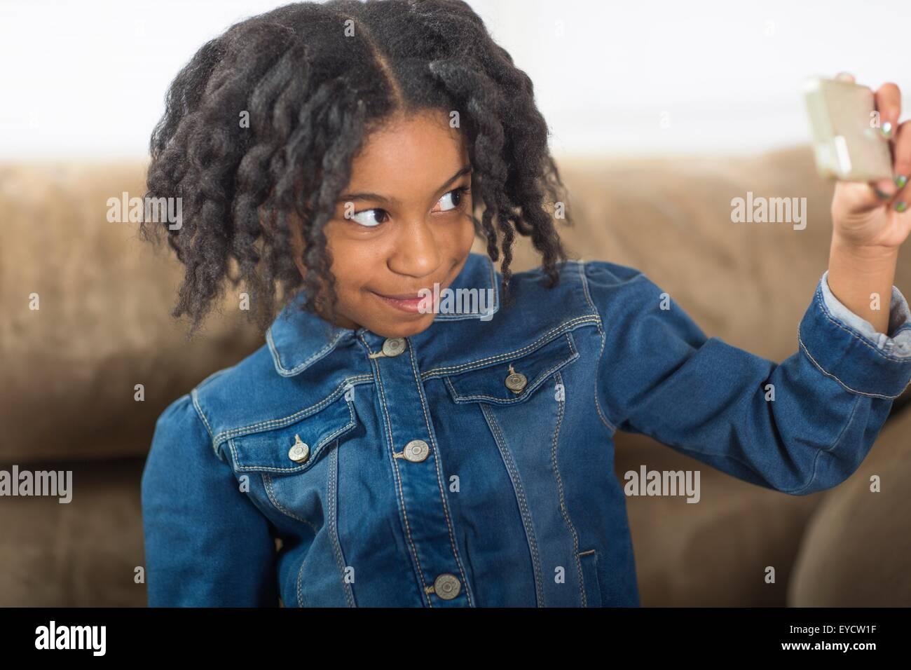 Jeune fille pour smartphone sur canapé selfies Photo Stock
