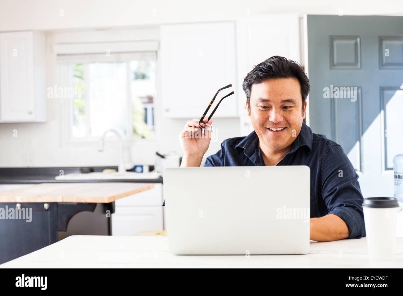 Smiling mature businessman typing on laptop in kitchen Photo Stock