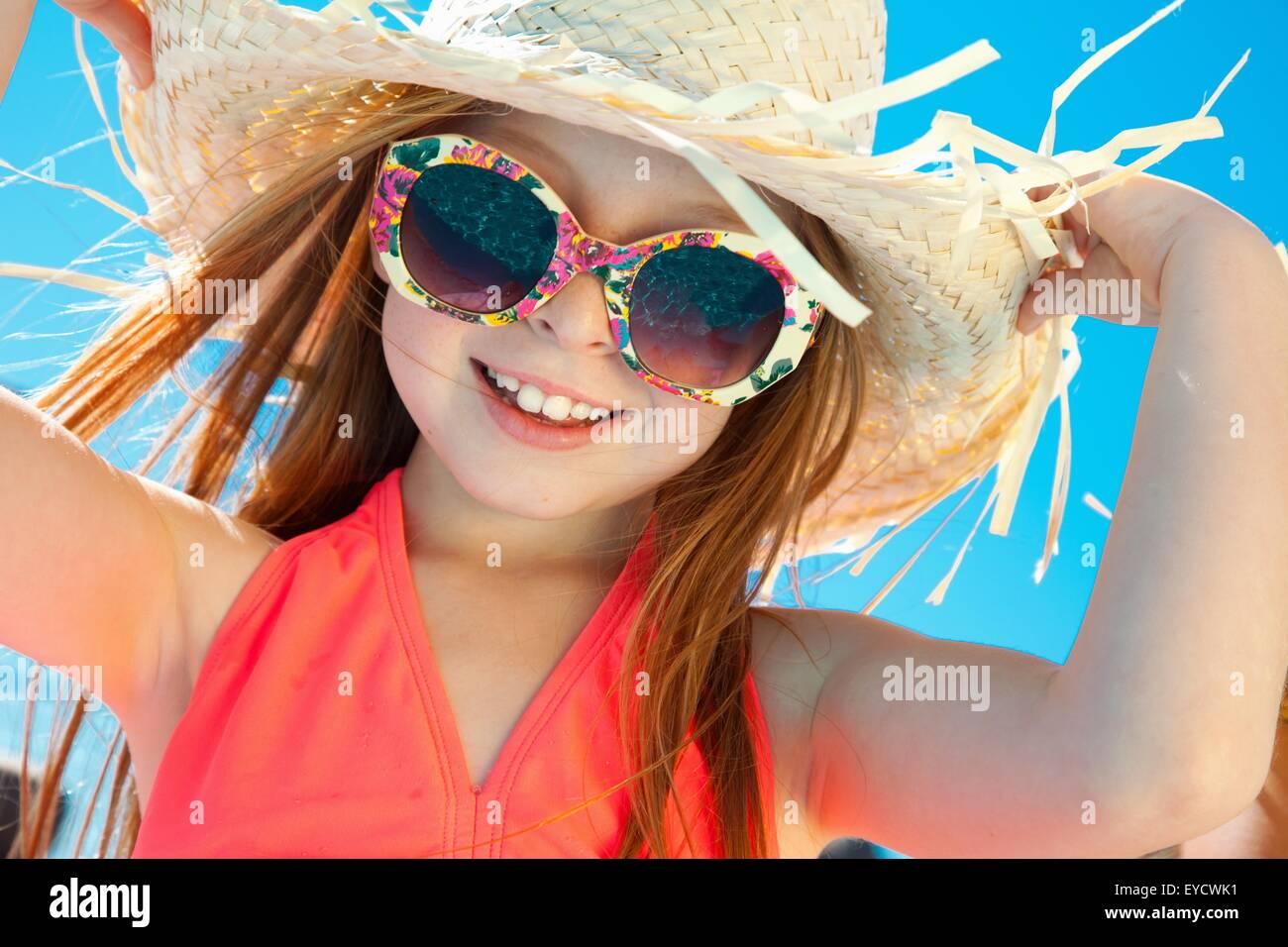 Jeune fille portant des lunettes de soleil et chapeau de paille Photo Stock