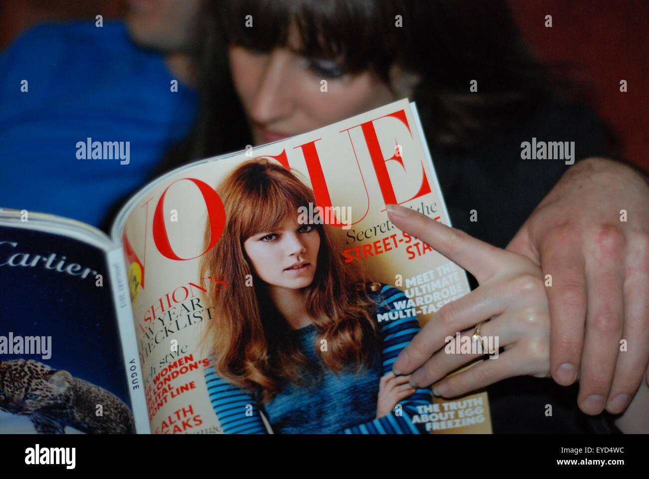 Un jeune couple nouvellement engagée sur un canapé. Elle consulte un magazine Vogue. Photo Stock