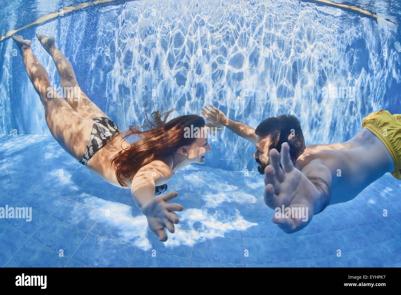 Happy senior couple on tropical honeymoon holidays - couple positif la natation et la plongée sous l'eau à la piscine Banque D'Images