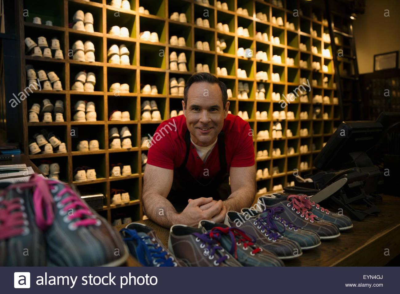 Portrait confiant travailleur au comptoir de location de chaussures de bowling Photo Stock