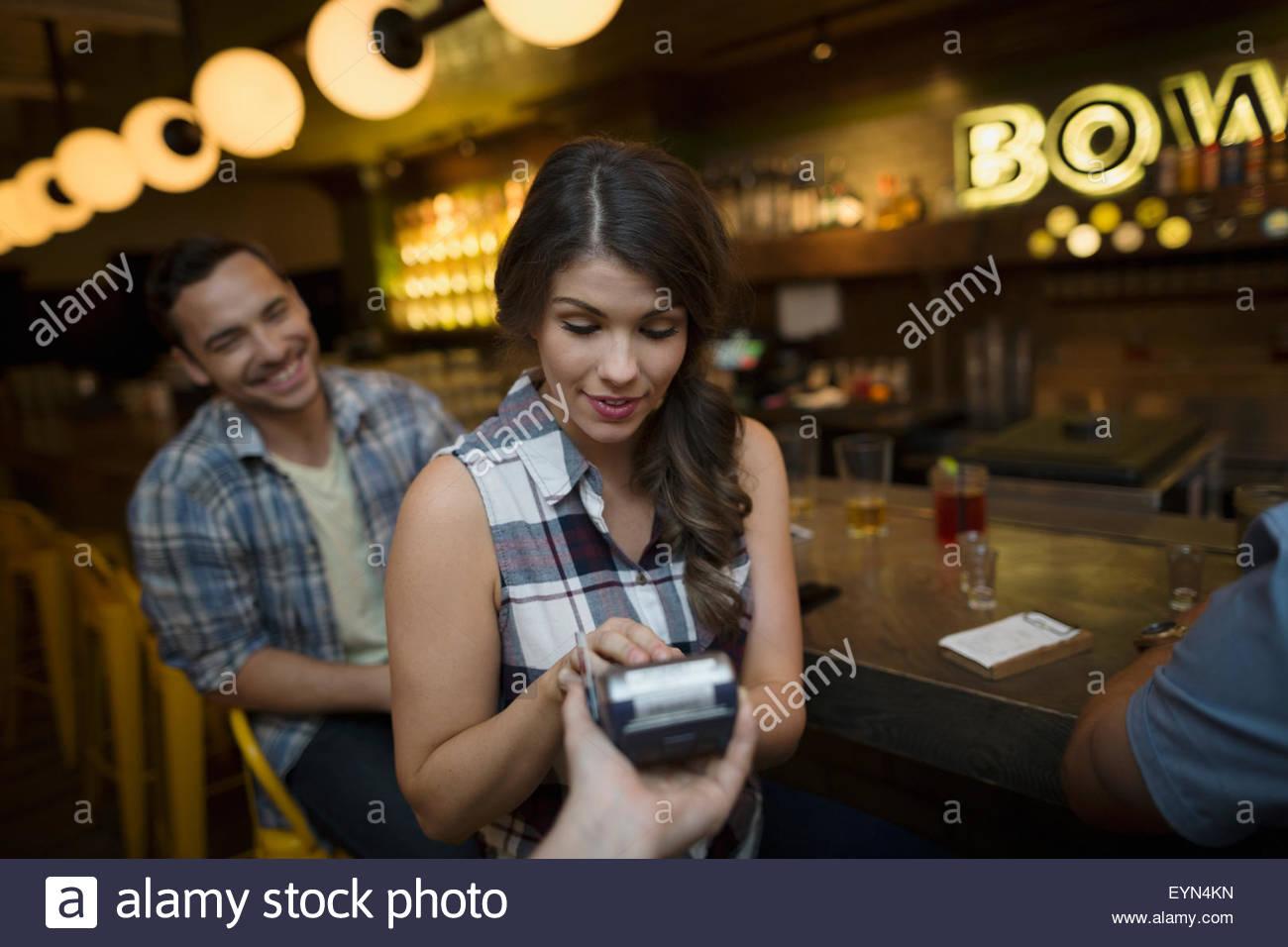 Les amis de payer pour le projet de loi au bowling bar Photo Stock