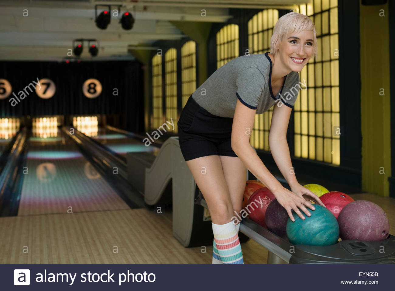 Smiling young woman choosing bowling ball du rack Photo Stock