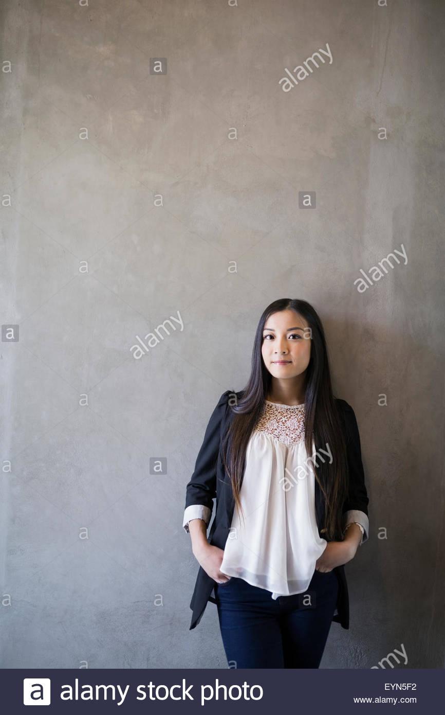 Portrait woman les mains dans les poches arrière-plan gris Photo Stock