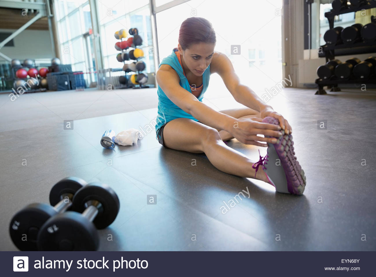 Woman stretching leg in gym Photo Stock