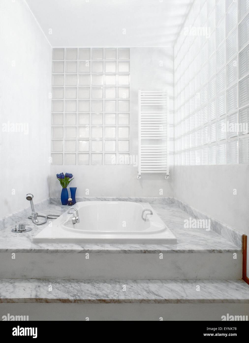 premier plan, une baignoire encastrée dans le sol surélevé de marbre