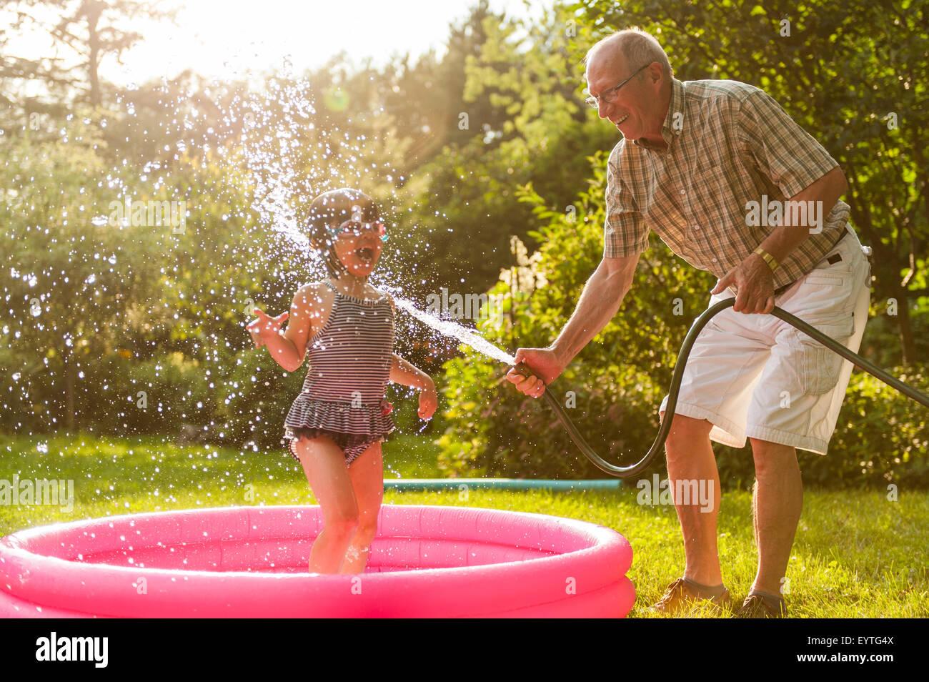 Les grands-parents et jouer avec le tuyau extérieur grandkid Photo Stock