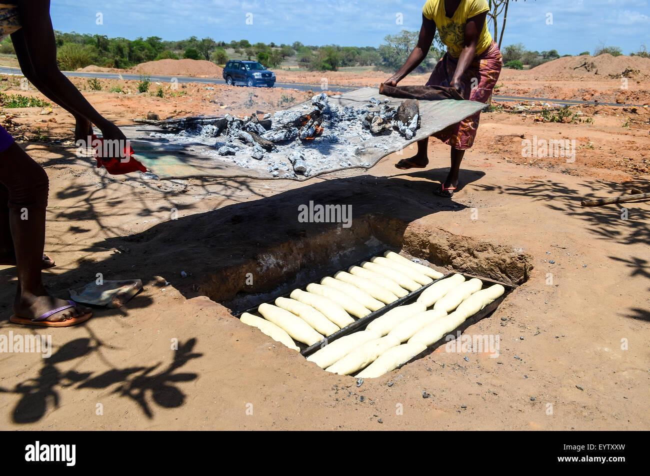 Les femmes angolaises la cuisson du pain dans le sol sous un feu Photo Stock