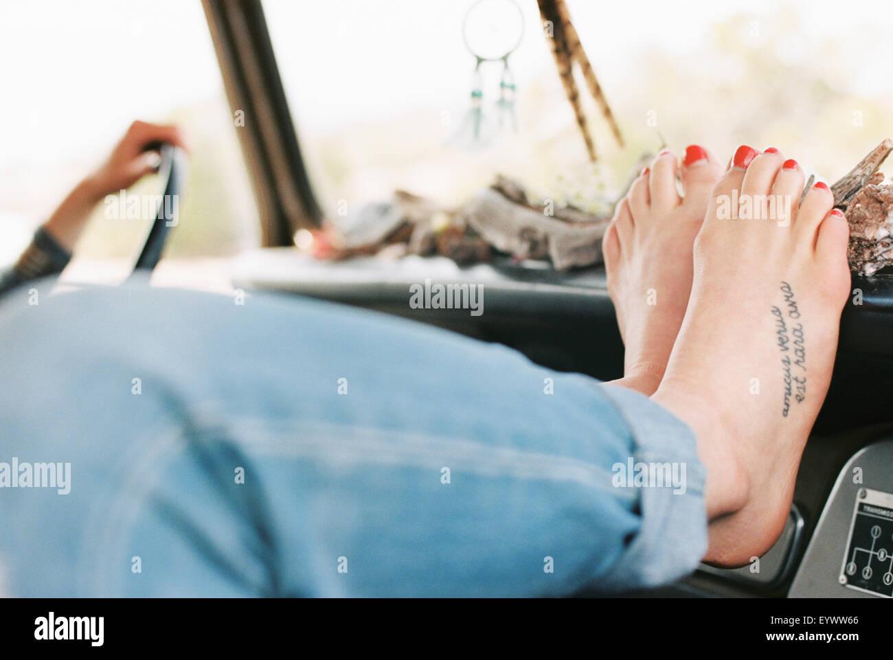 Femme aux pieds nus reposant ses pieds sur le tableau de bord d'un 4x4, un tatouage sur son pied droit. Photo Stock