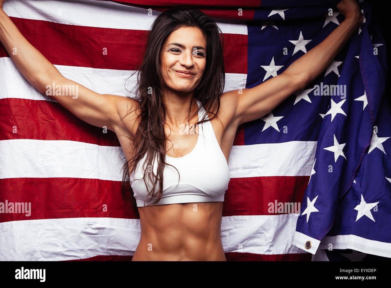 Portrait of happy young woman in sportswear holding drapeau américain en souriant. Mettre en place l'athlète féminine Banque D'Images