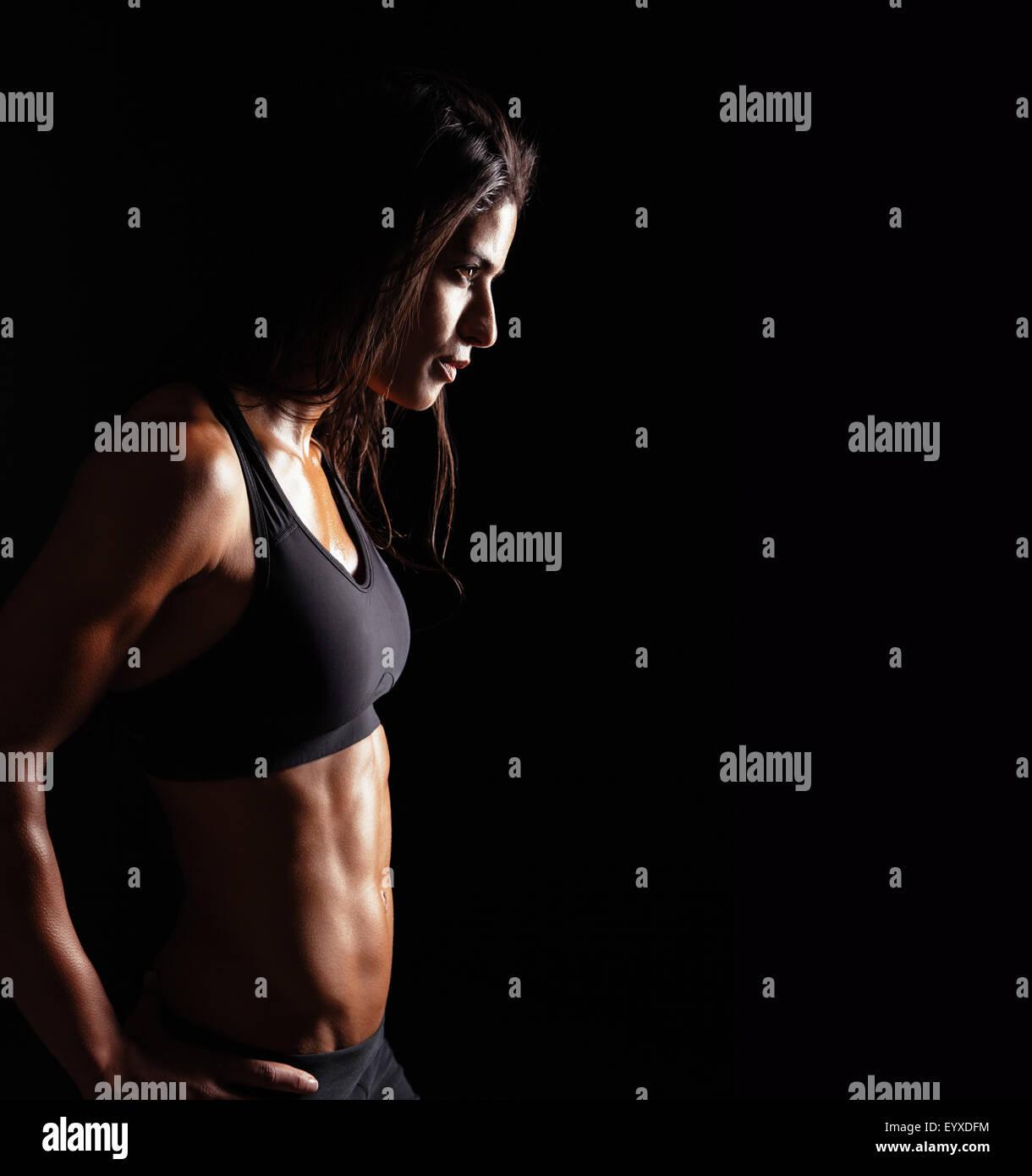 Image de la femme dans les vêtements de sport fitness à la voiture sur fond noir. Jeune femme avec un Photo Stock