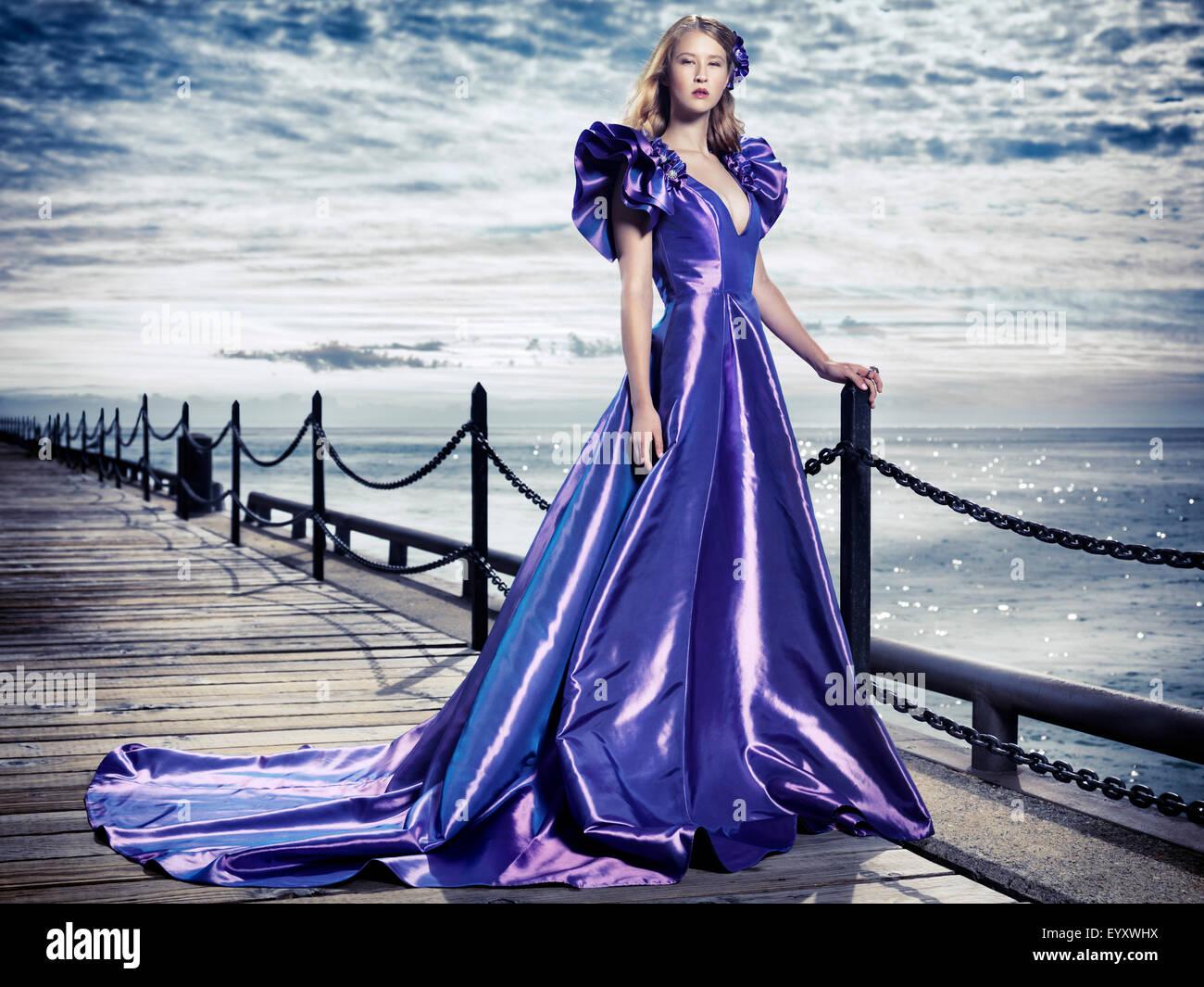 Jeune femme portant une belle et longue robe de soirée bleu debout à bord de l'eau, fashion portrait Photo Stock