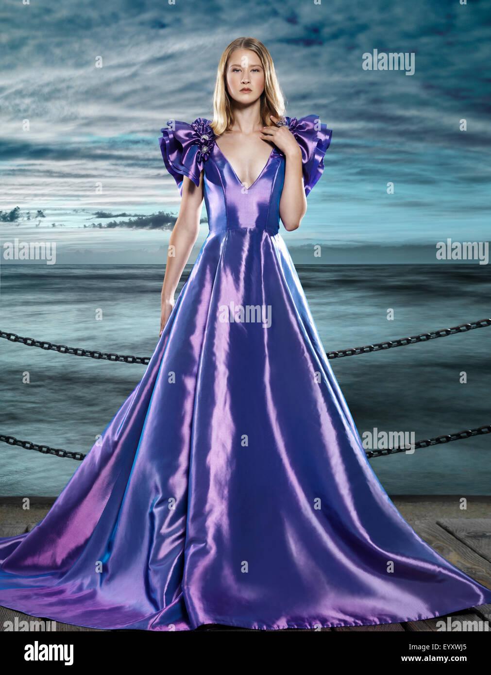 Jeune femme blonde vêtue d'une belle et longue robe bleue, robe du soir, à bord de l'eau, fashion Photo Stock