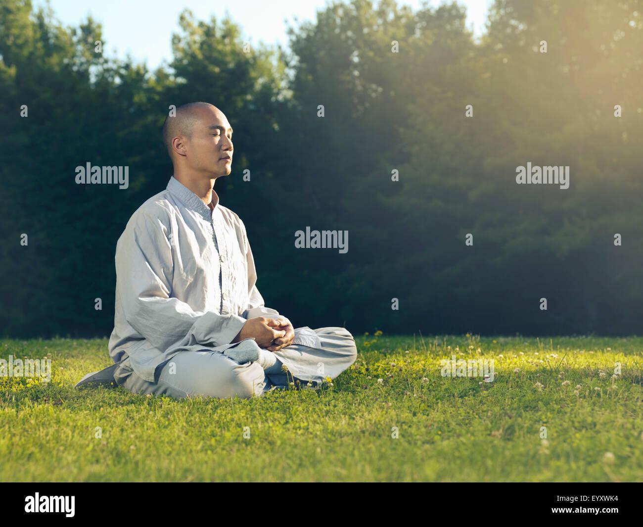 Moine Shaolin méditer en plein air dans la nature au lever du soleil, assis sur l'herbe dans la lumière du soleil Banque D'Images