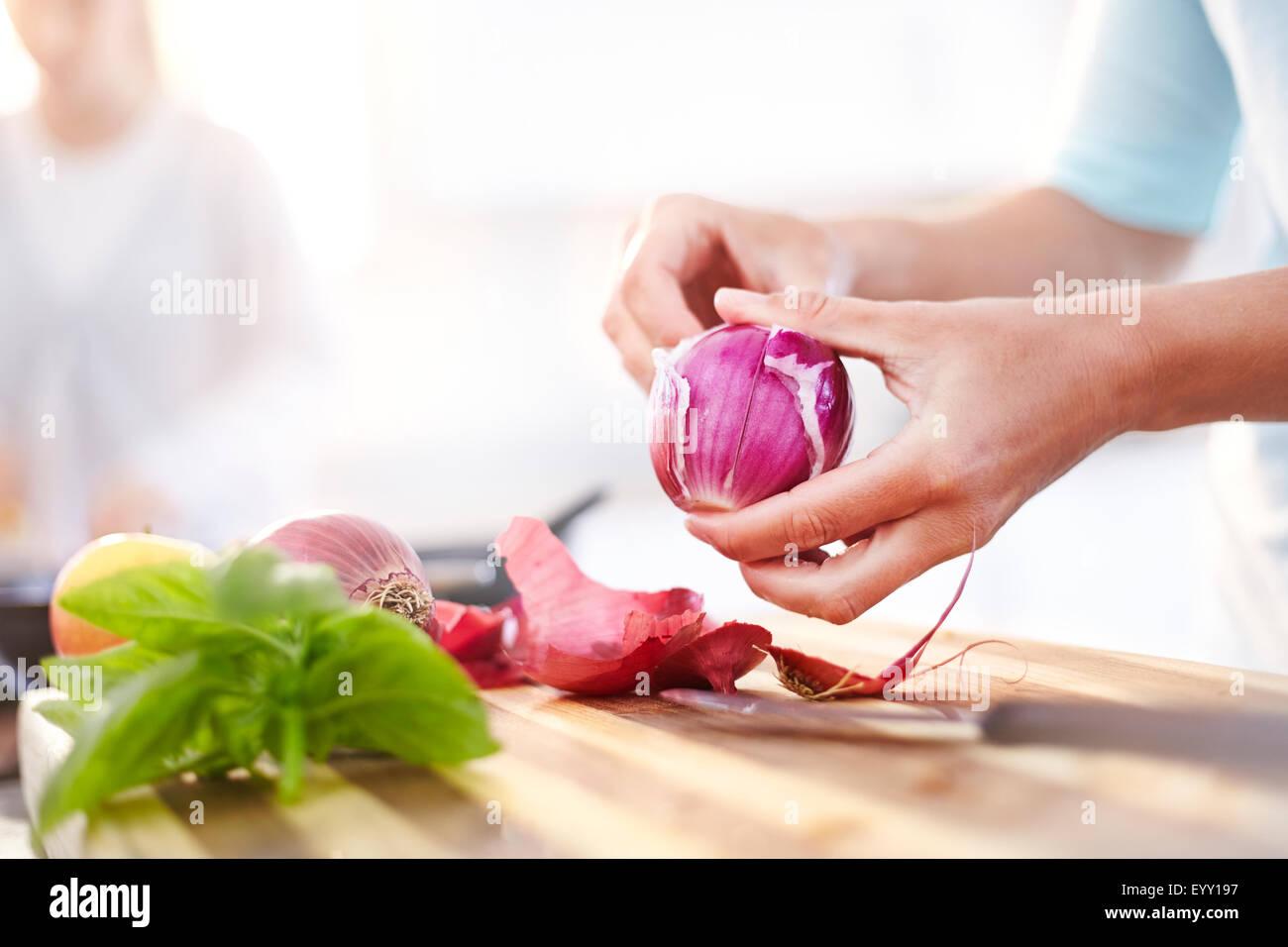 Woman peeling oignon rouge dans la cuisine Photo Stock