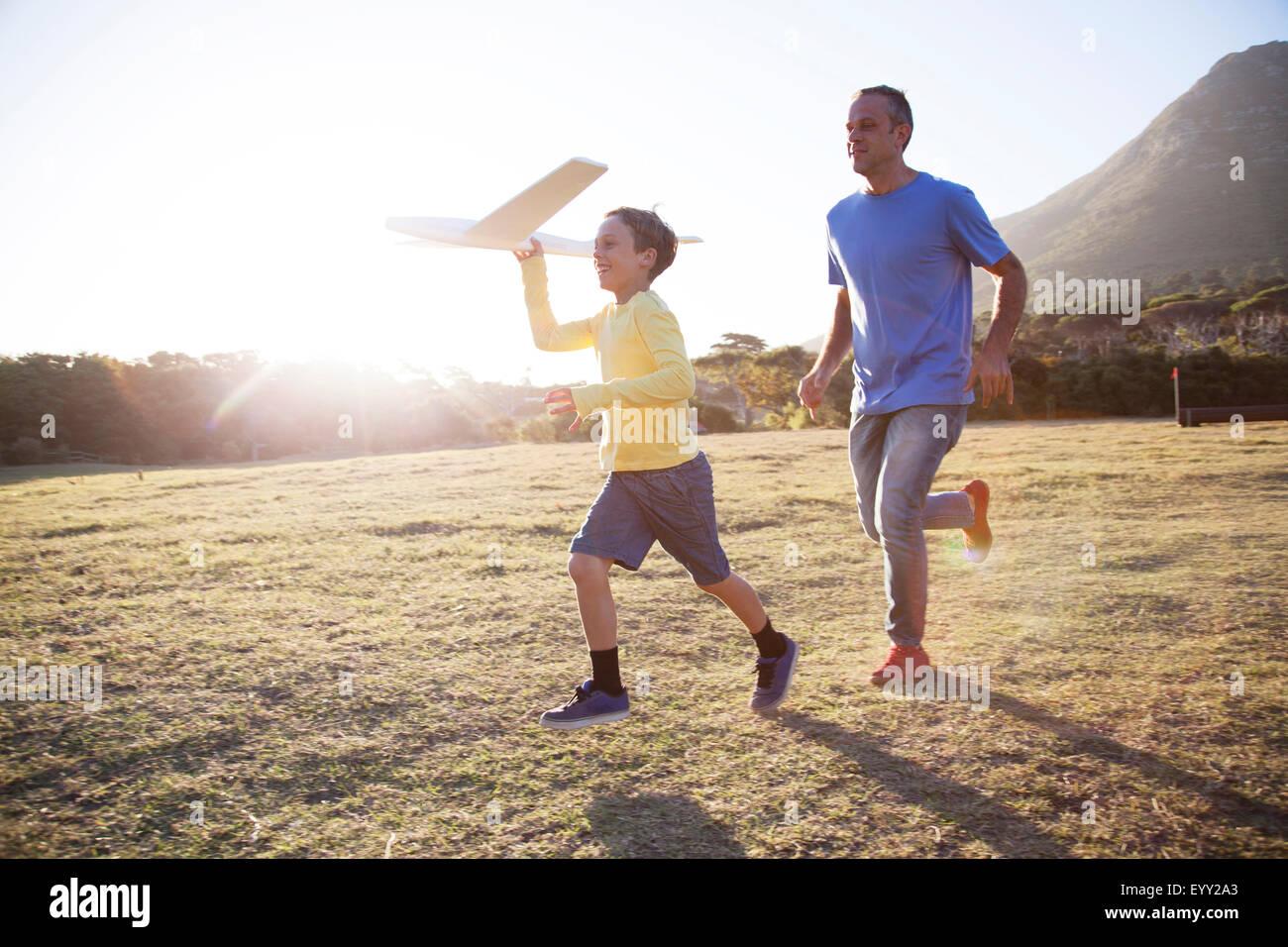 Portrait père et fils flying model airplane in field Banque D'Images