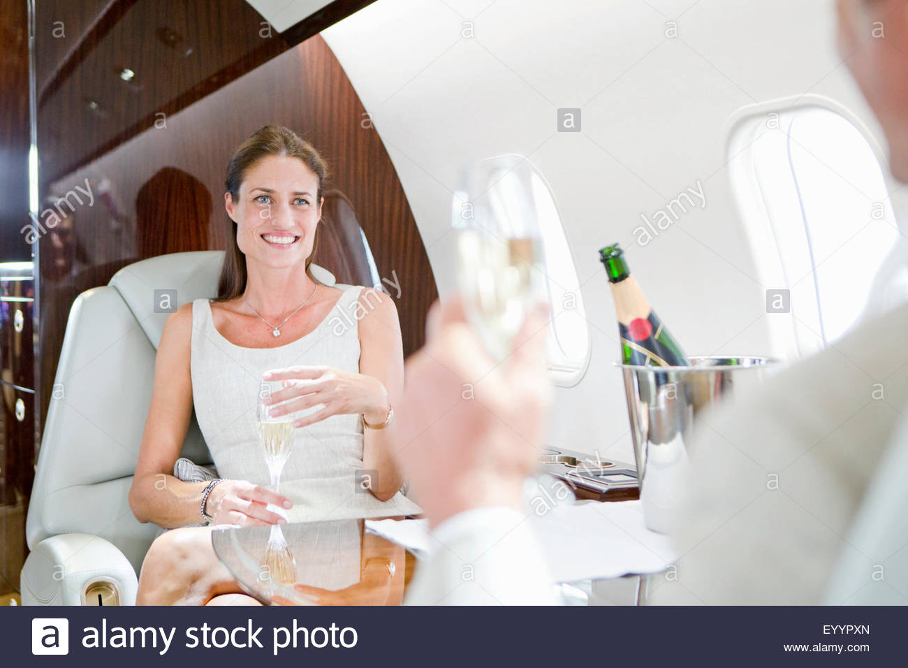 Belle smiling couple drinking champagne on private jet Photo Stock