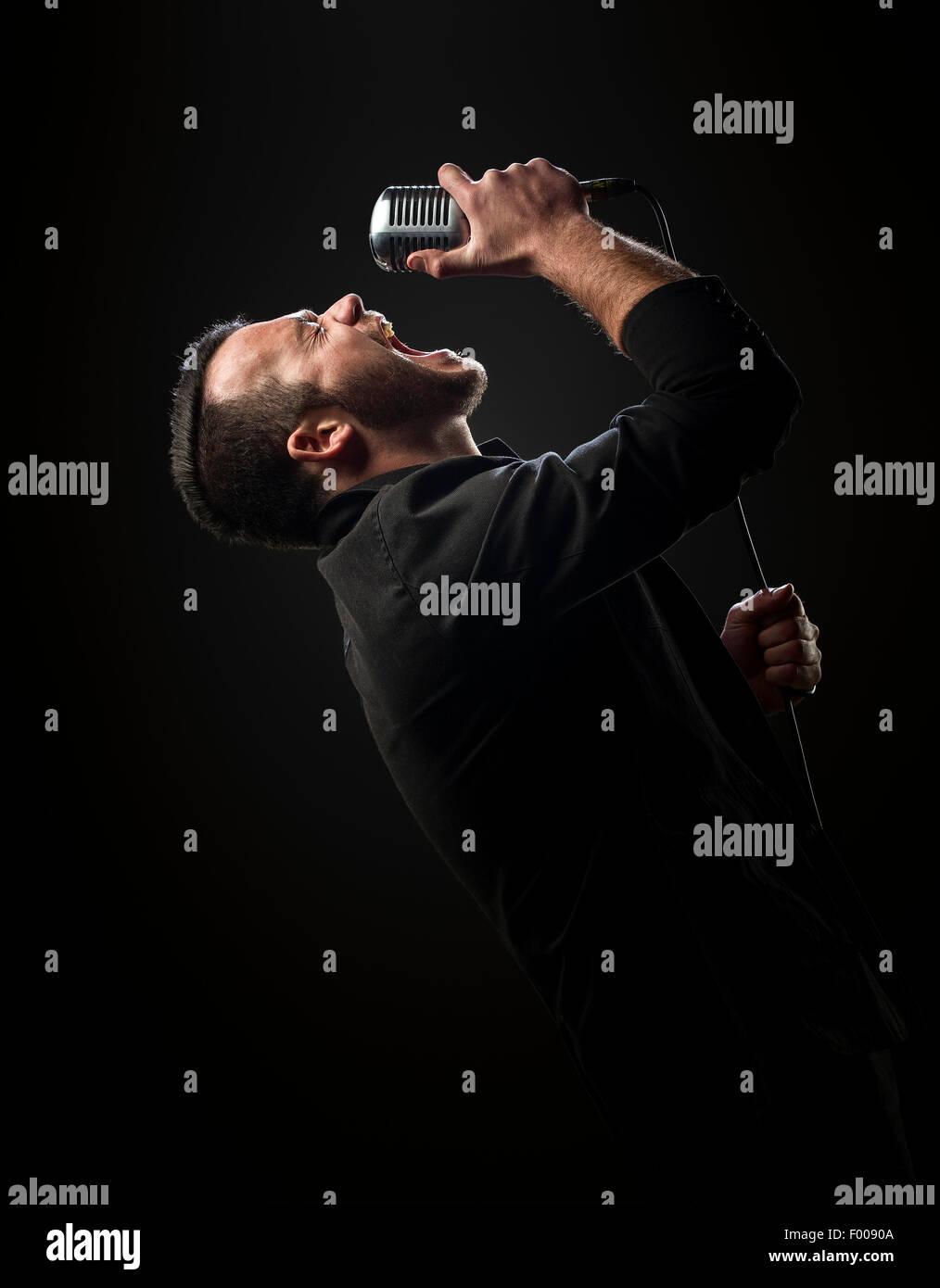 Singer l'exécution avec microphone sur un fond sombre Photo Stock