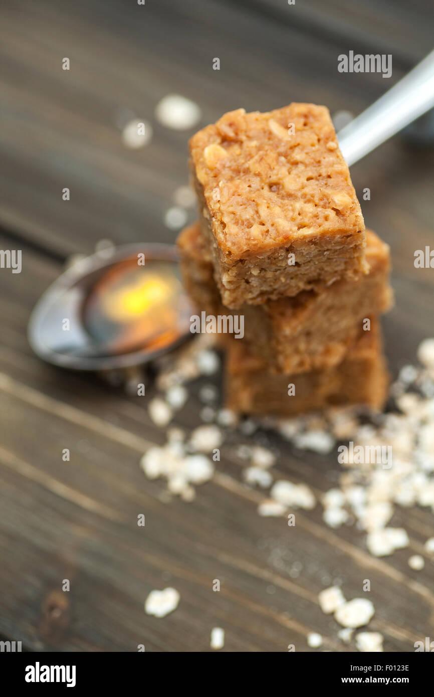 Pile de gommeux et indulgente flapjacks sur un fond de bois entouré par des ingrédients Banque D'Images