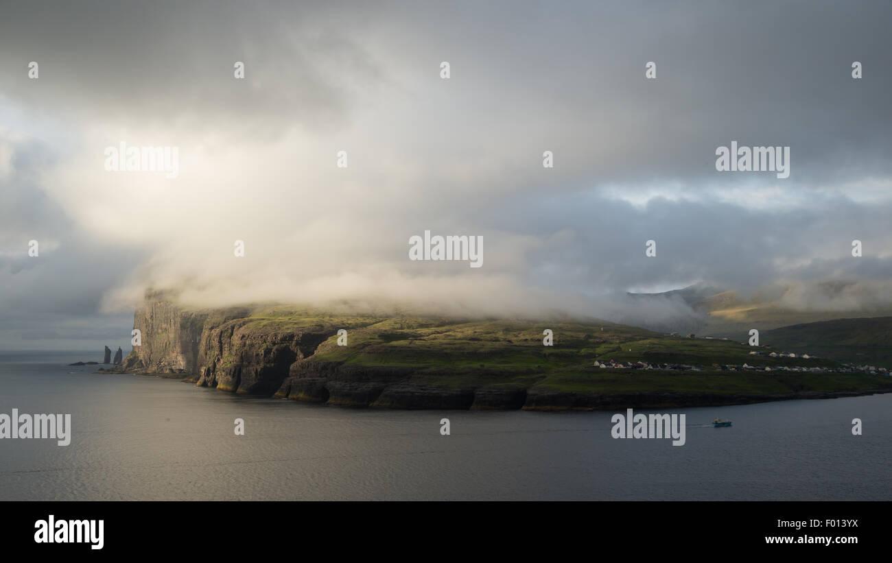 La hausse et Kellingin cheminées et Eidi village sur l'île de Eysturoy vu de Tjornuvik. Îles Photo Stock