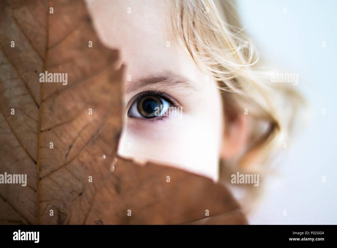 Portrait d'une jeune fille se cacher derrière leaf Photo Stock