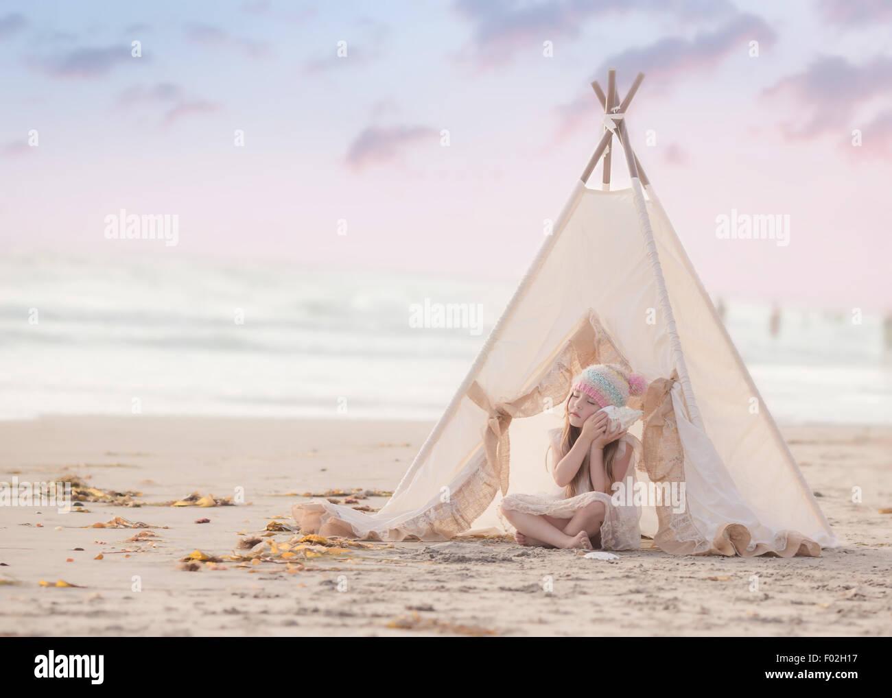 Fille assise dans un wigwam sur la plage de l'écoute d'un coquillage Photo Stock