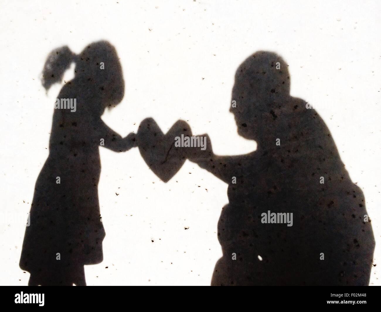Ombre d'une fille de remettre son père un cœur Photo Stock