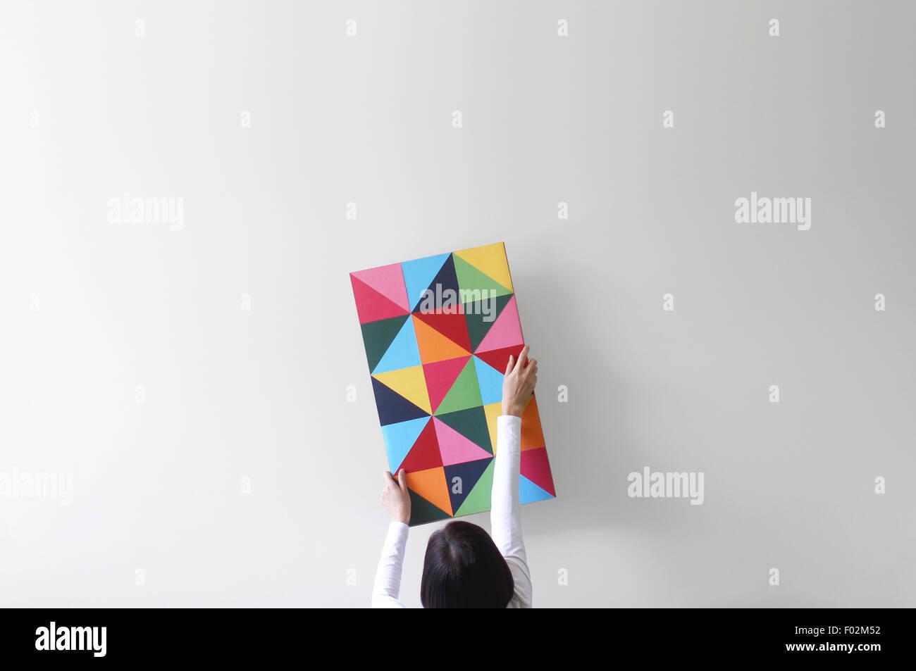 Femme décorant un mur blanc vide avec des œuvres d'art colorées Photo Stock