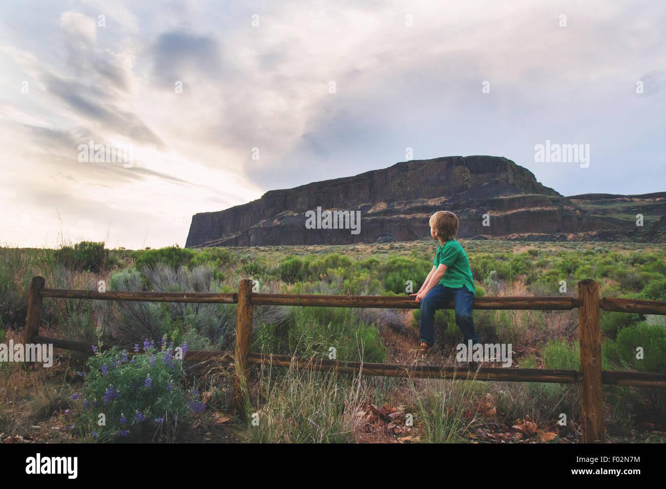 Garçon assis sur la clôture en bois regardant par-dessus son épaule Photo Stock