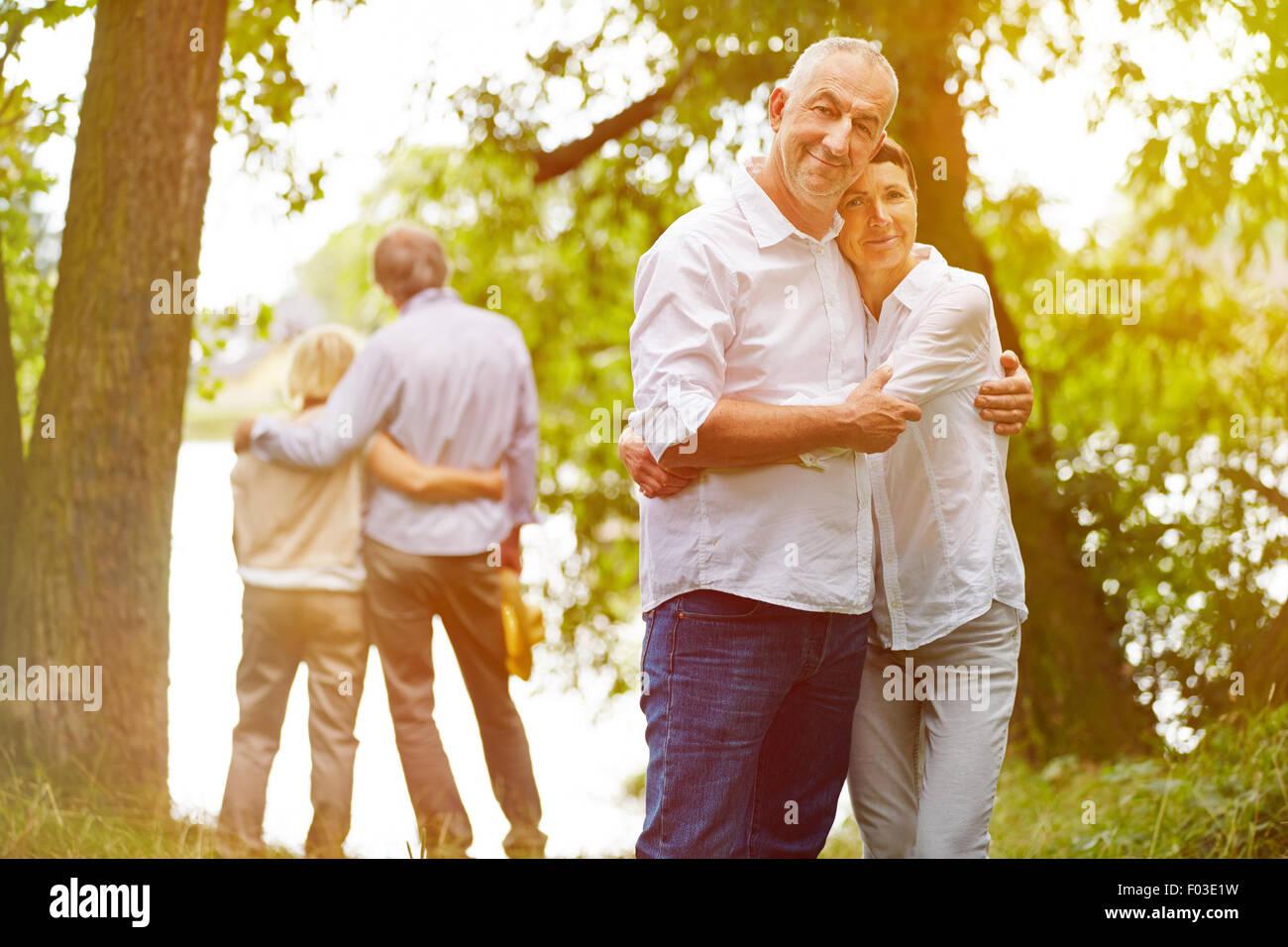 Deux heureux couples aînés dans des foyers de jardin en été Photo Stock