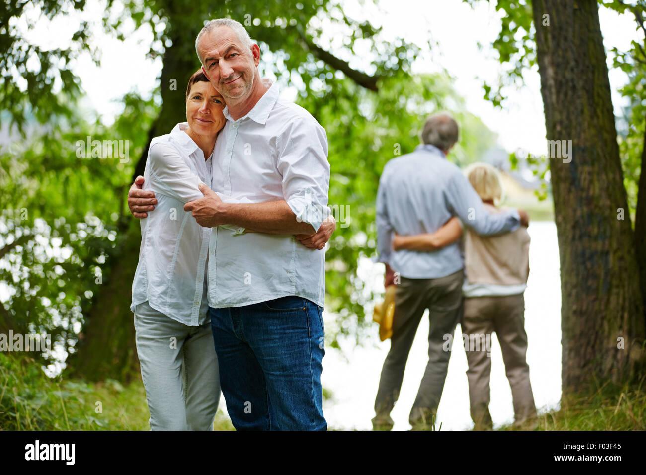 Deux heureux couples aînés englobant dans jardin de maison de retraite Photo Stock