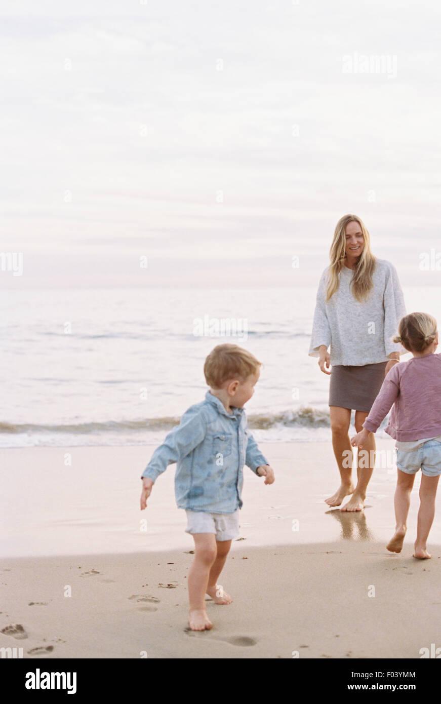 Femme jouant avec son fils et sa fille sur une plage de sable fin à l'océan. Banque D'Images