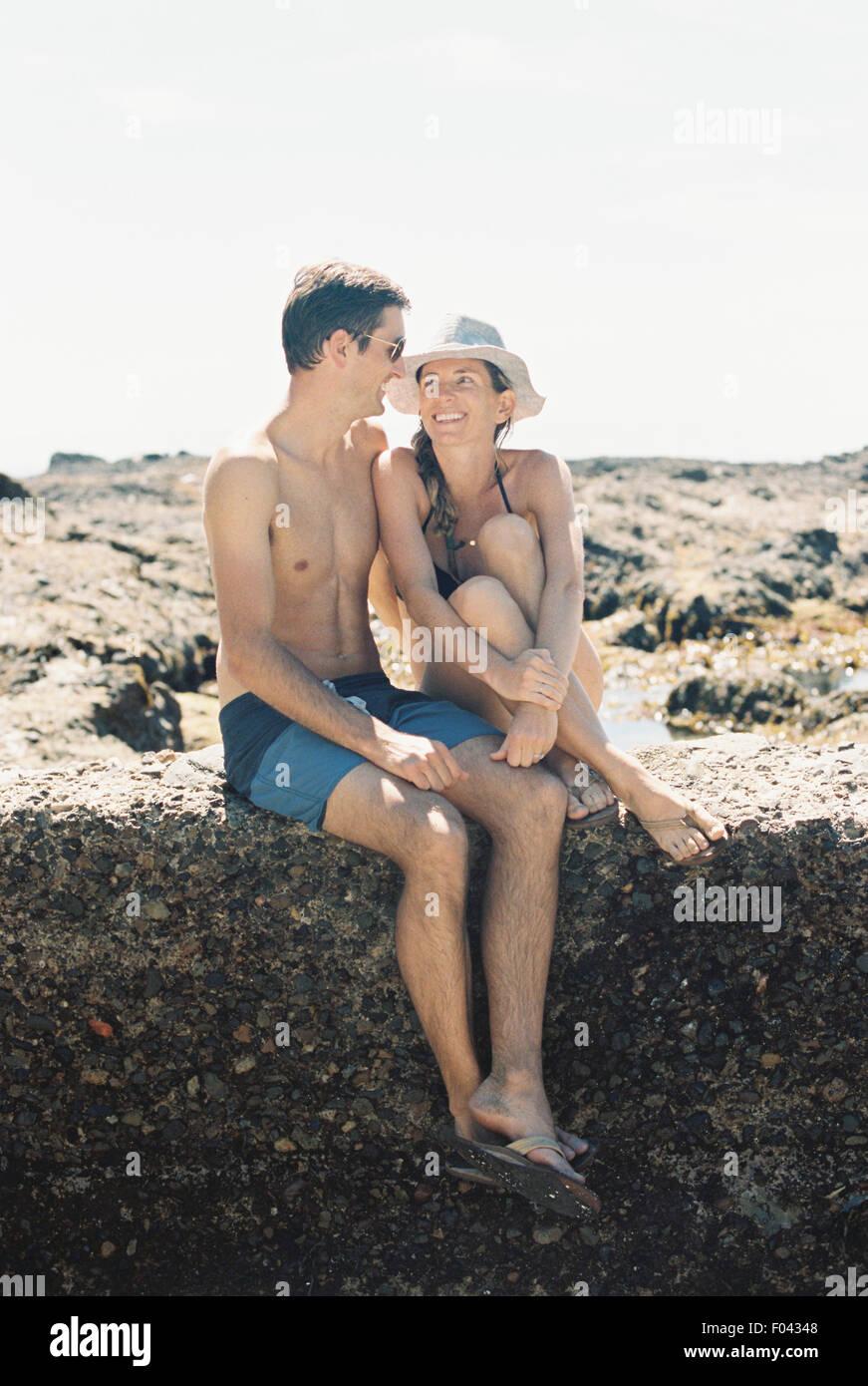Un homme et une femme, un couple assis sur la plage à l'autre avec amour Photo Stock