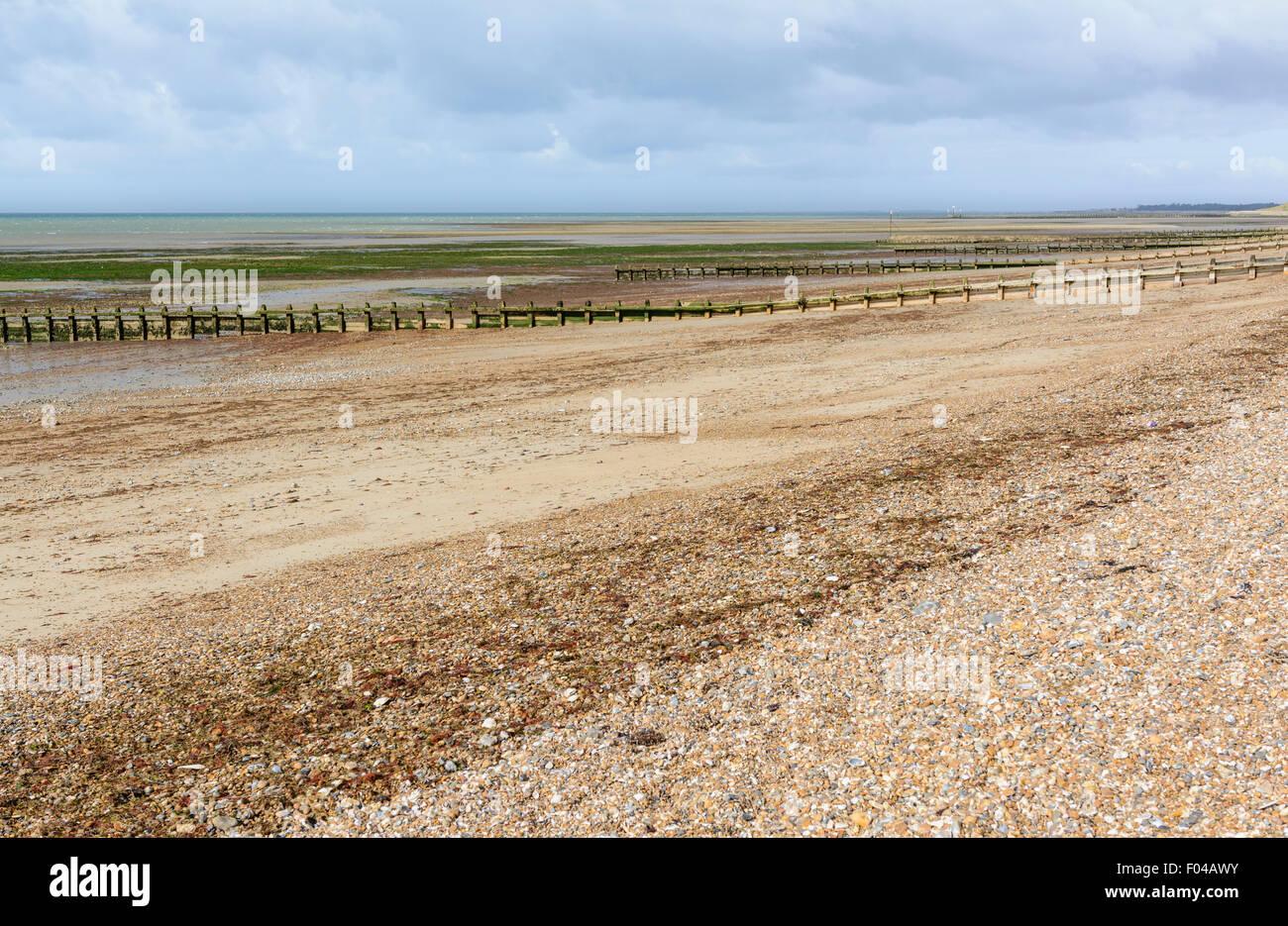Plage de galets désertes à marée basse. Photo Stock