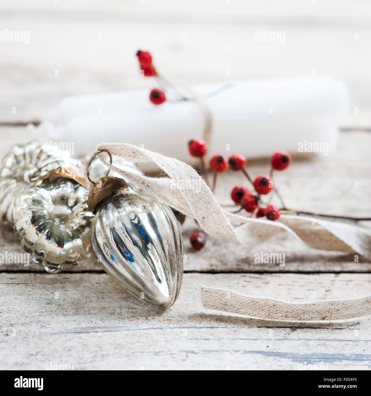Les bougies blanches attachées avec de la ficelle, fruits rouges et argent baubles Photo Stock