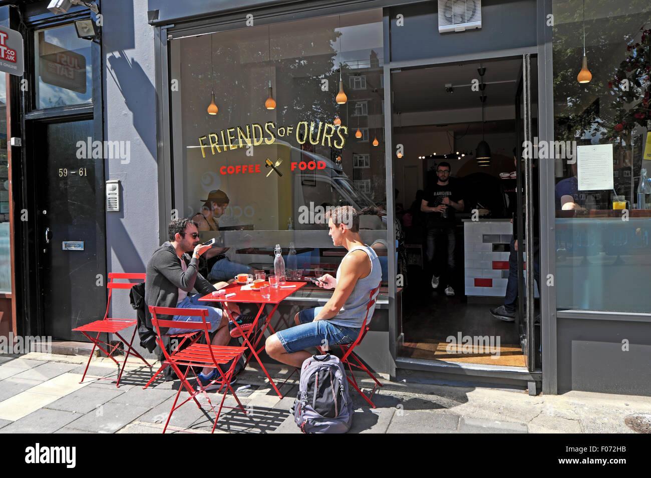 Les jeunes hommes assis à table dehors 'amis' cafe dans maison Pitfield, Hoxton East London UK KATHY Photo Stock