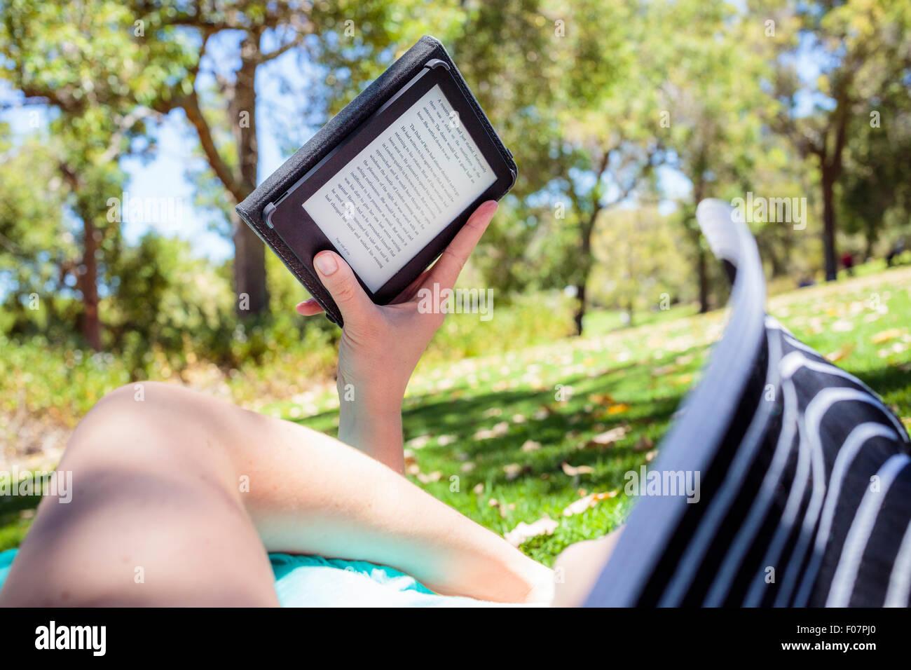 Une femme dans un parc de lire un livre sur un e-reader Photo Stock