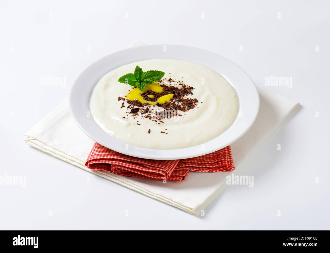 Bouillie de semoule en douceur servi avec du chocolat râpé et le lait caillé de citron Photo Stock