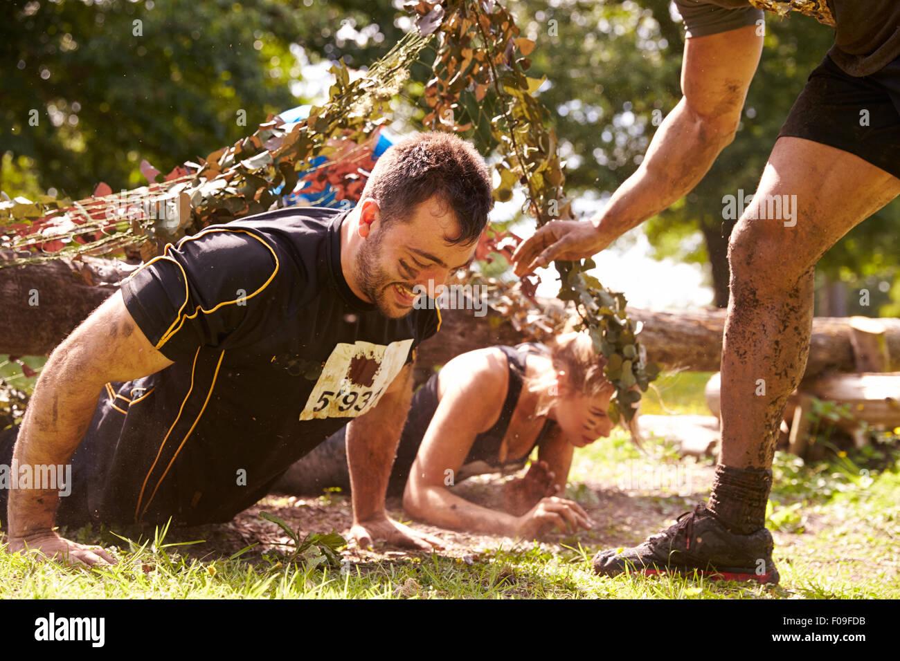 Parcours du combattant, d'aider les autres concurrents ramper sous des moustiquaires Photo Stock