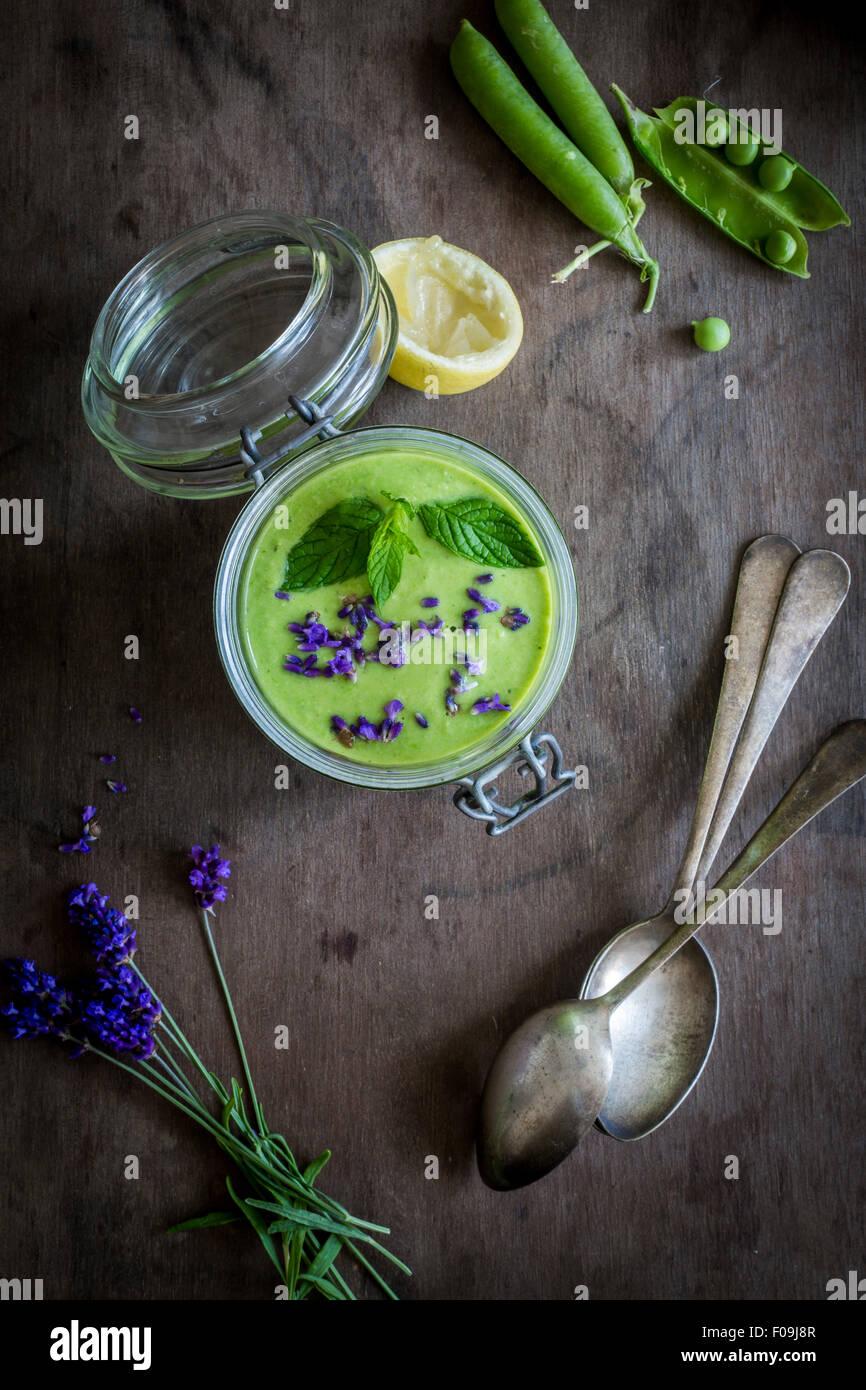 Gaspacho vert en pot avec des petits pois et de lavande sur fond de bois vintage avec cuillères. Vue d'en haut Banque D'Images