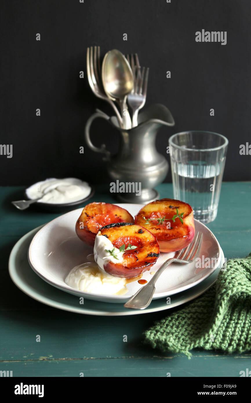 Plaque avec peach grillés avec du yaourt grec et au miel et décoré avec du thym frais Photo Stock