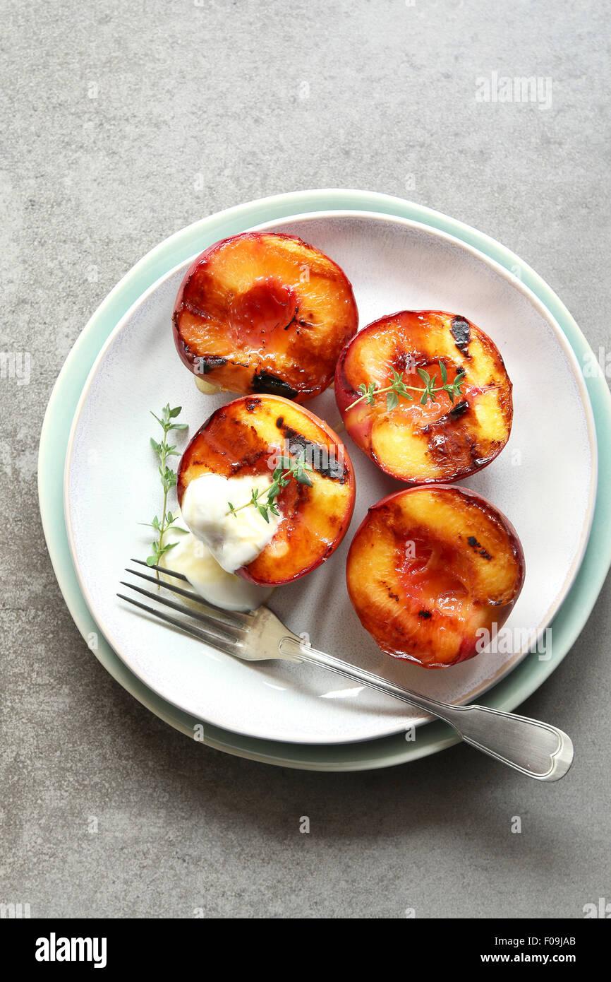 Plaque avec peach grillés avec du yaourt grec, miel et décoré avec du thym frais Photo Stock