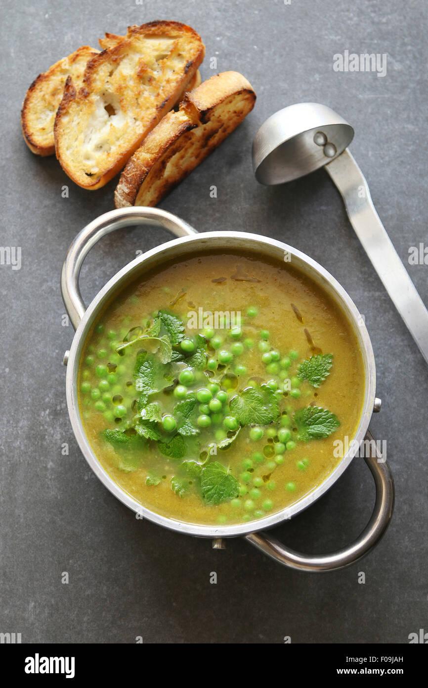 Soupe aux pois verts dans une casserole en aluminium garnis de menthe fraîche Photo Stock