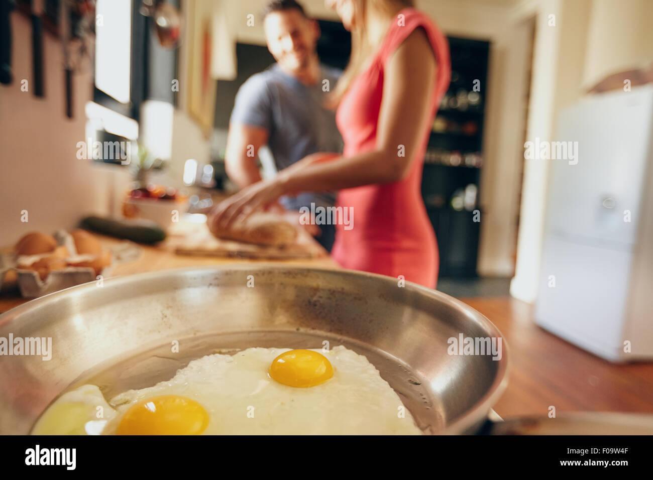 Oeufs frits à la poêle avec couple standing en arrière-plan ne sont pas mise au point en cuisine Photo Stock
