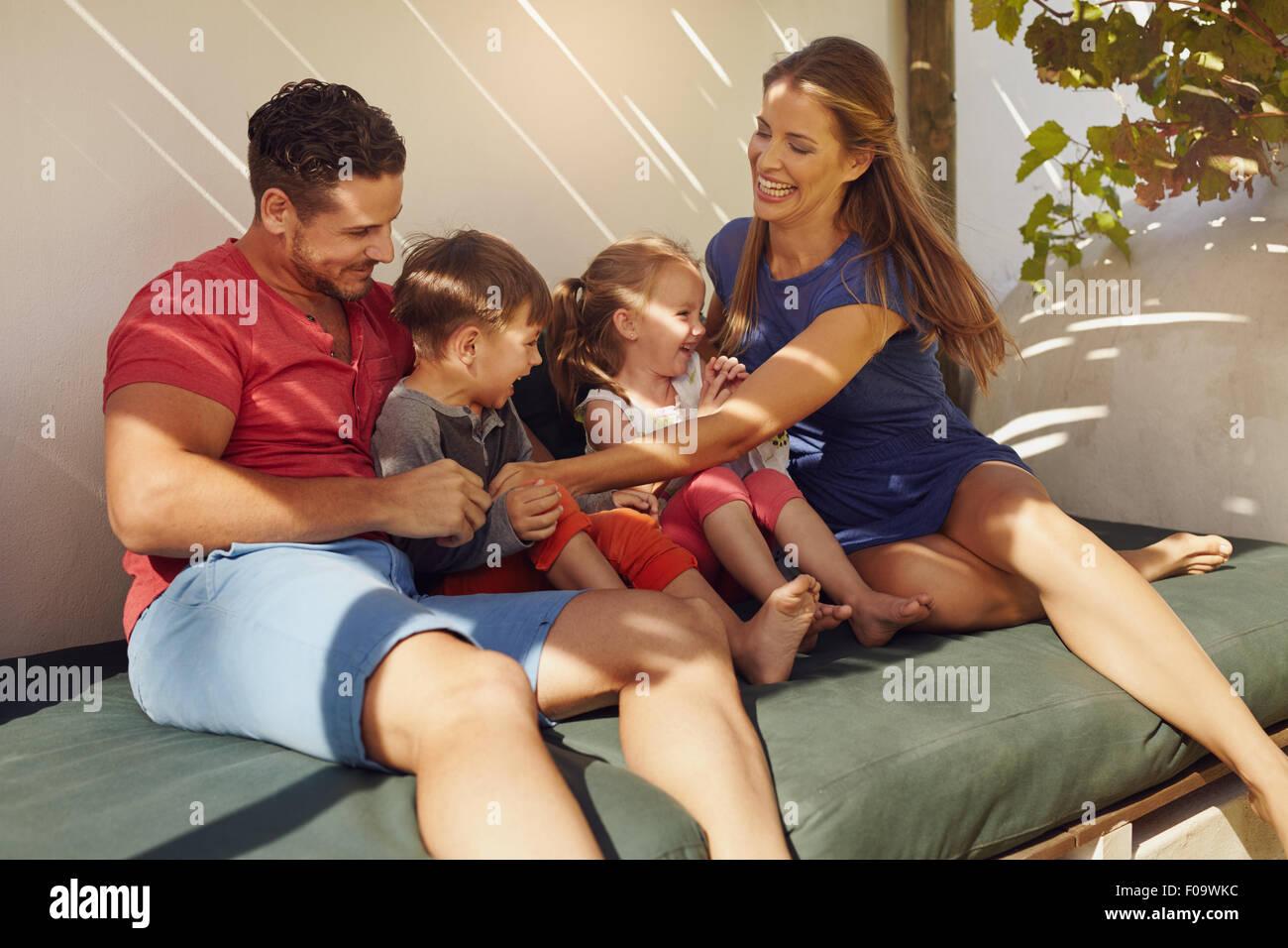 Coup de jeune famille heureux assis ensemble dans le patio. Couple avec leurs enfants assis sur la table dans la Photo Stock