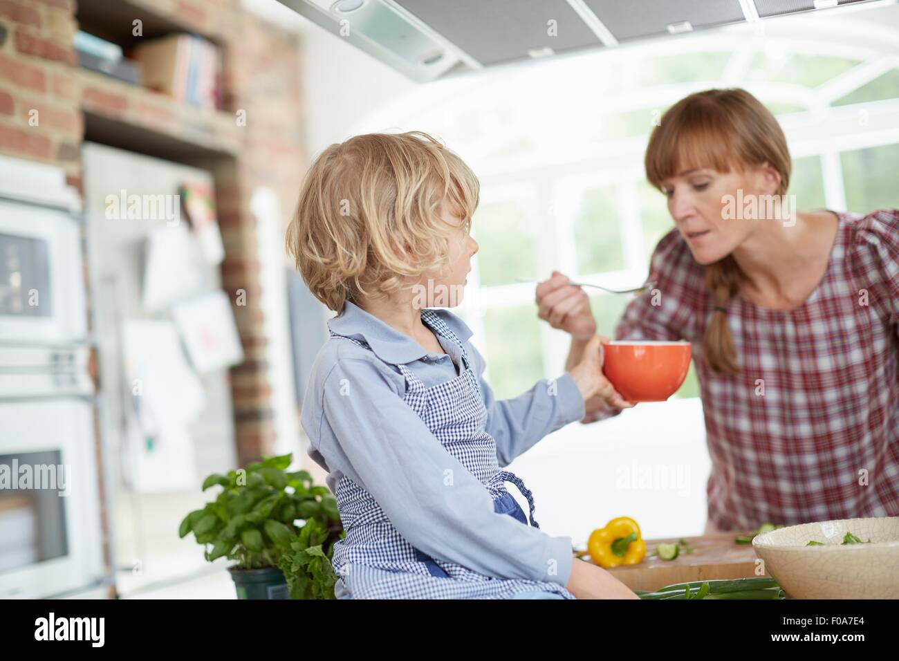 Mère et fils preparing meal in kitchen Photo Stock