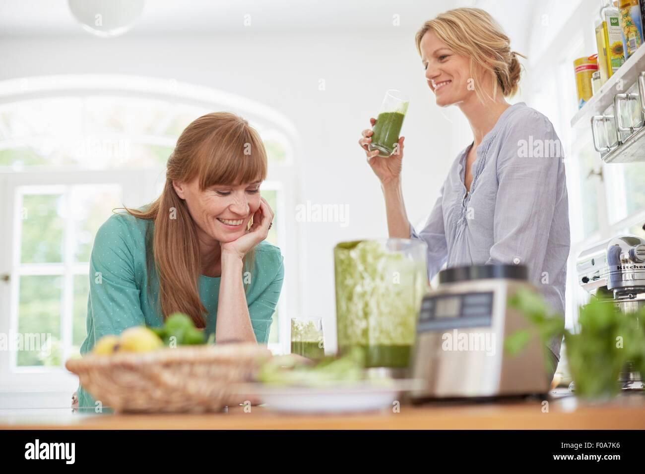 Les femmes végétaliennes vert potable dans la cuisine smoothie Photo Stock
