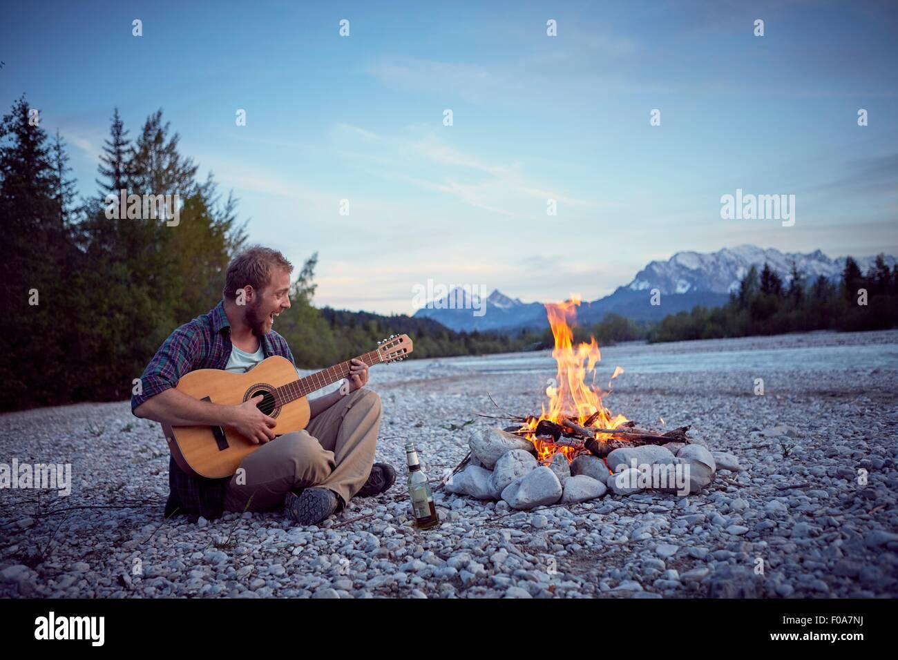 Jeune homme assis par camp à jouer de la guitare, chant, Wallgau, Bavière, Allemagne Photo Stock