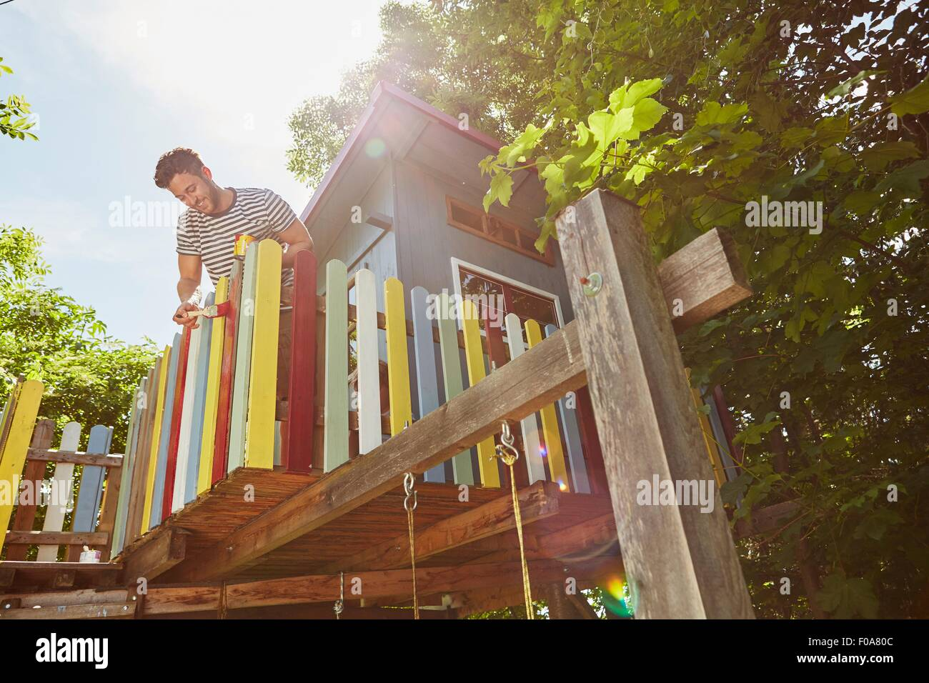 Jeune homme peinture tree house, low angle view Photo Stock